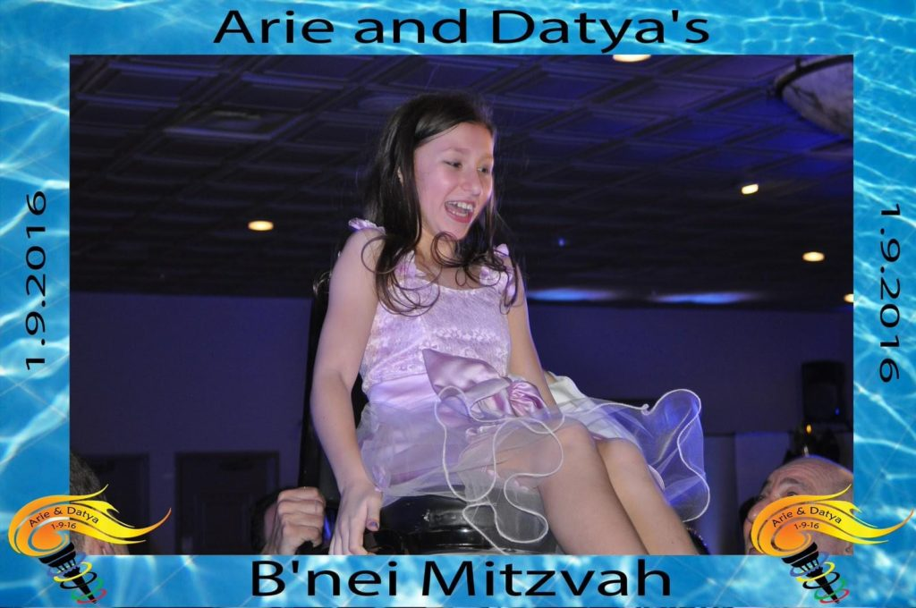a girl is raised on a chair at her bat mitzvah