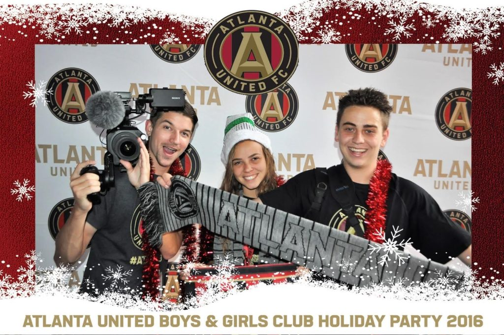 three people pose for a mag-nificent picture at an Atlanta United holiday party