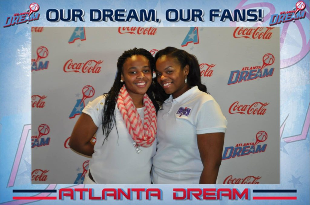 two girls pose for a mag-nificent photo at an Atlanta dream game