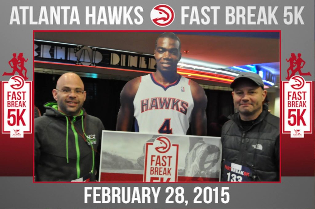two guys pose for a mag-nificent photo at an atlanta hawks promotional event