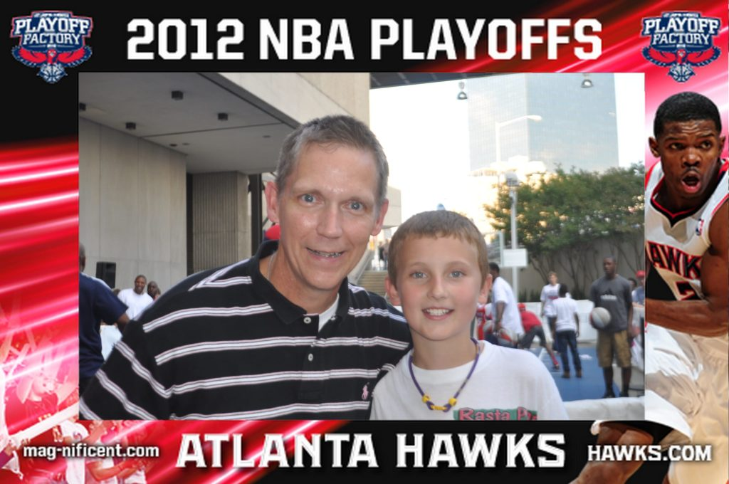 a father and son pose for a mag-nificent picture at a hawks game