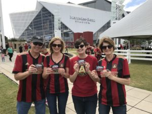 a group of people hold up mag-nificent photo magnets at an atlanta united game