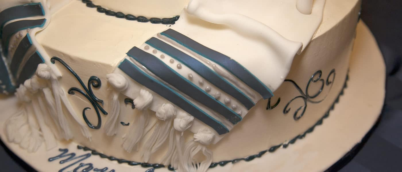 Blue and white Bar Mitzvah cake with tallis decoration and Mazel Tov written on it.