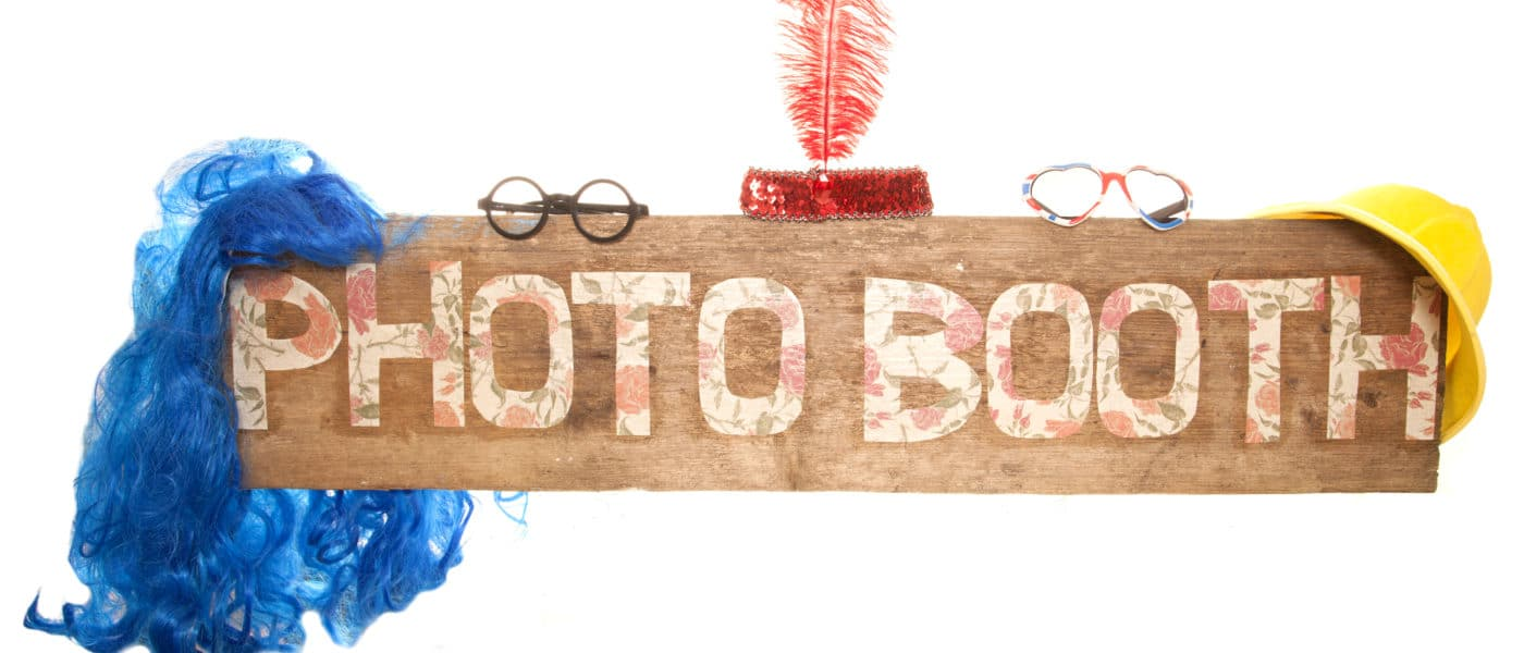 """Photo Booth"" imprinted on a wooden plank with photo booth accessories as decorations."