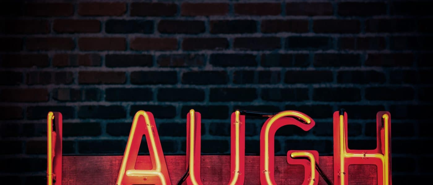 "Neon sign infront of a brick wall that spells the word ""laugh."""