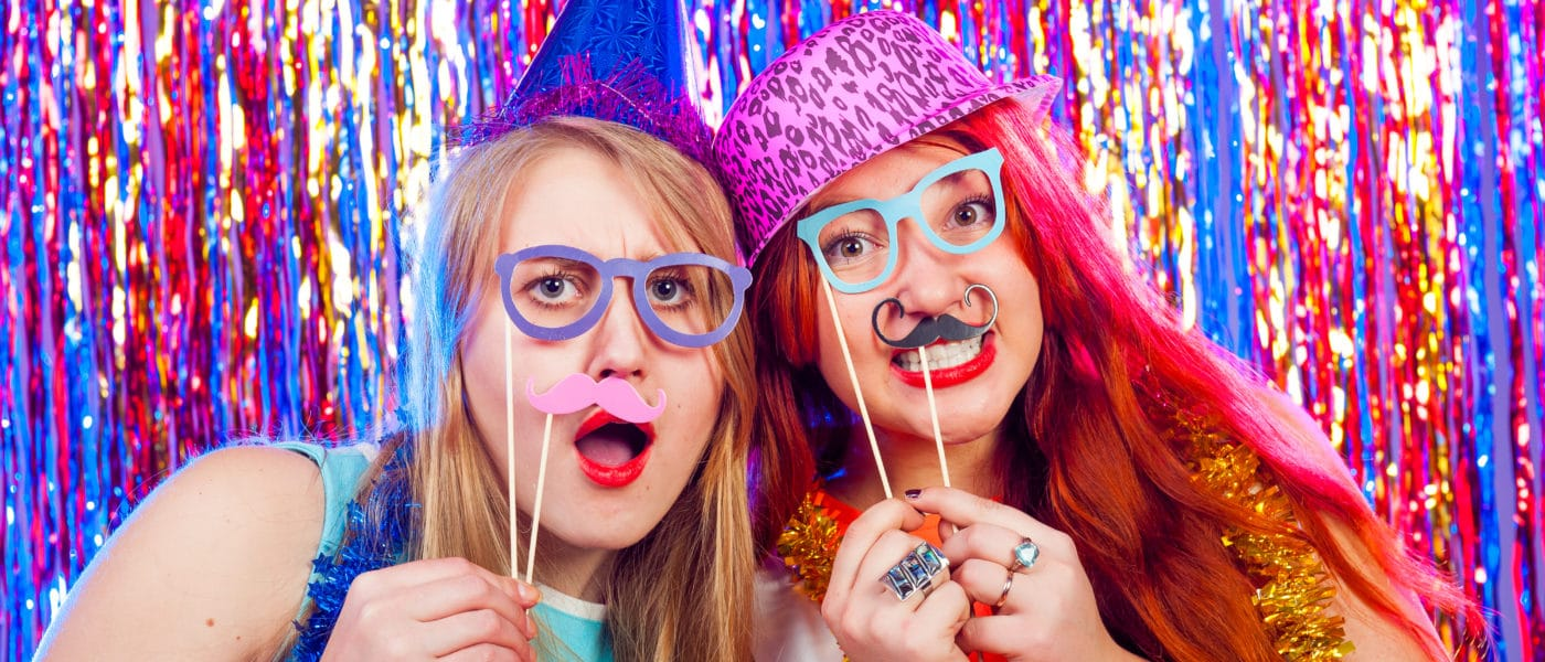 Young girls posing for a picture in a selfie booth.