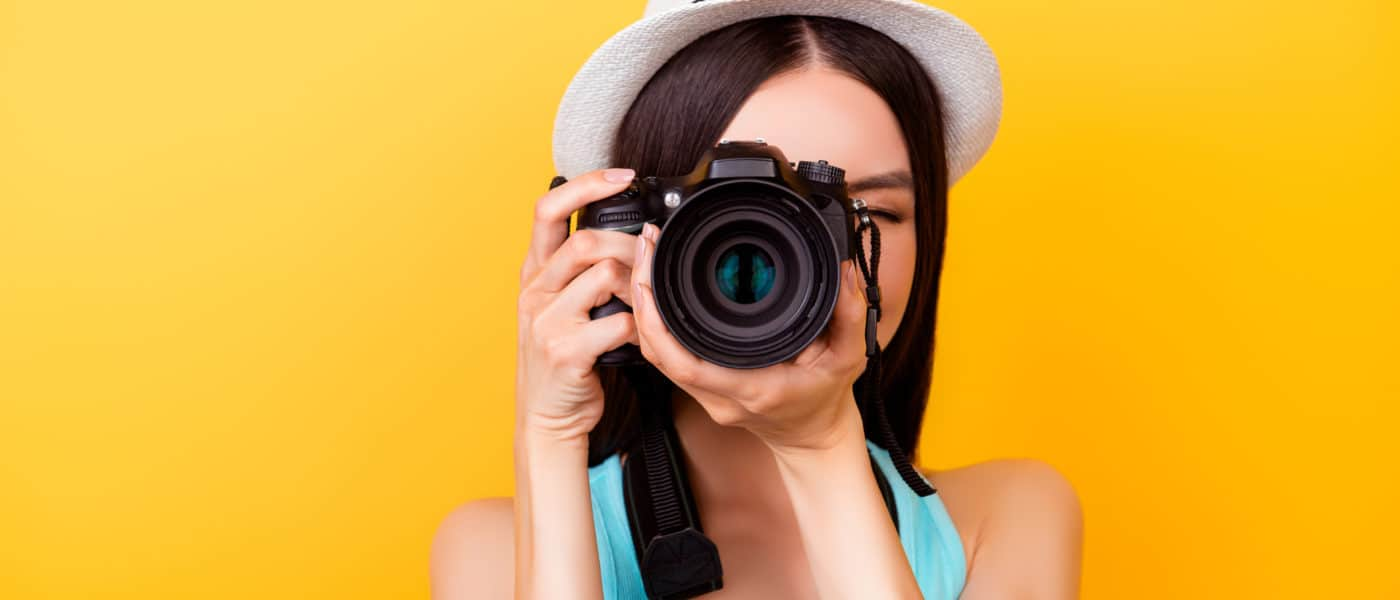 Picture of a woman with a camera in front of a yellow background.