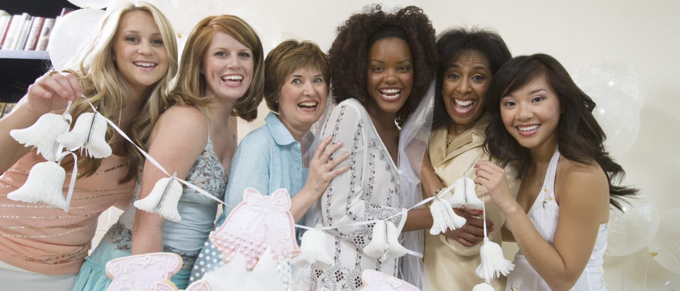 Group of women posing holding bridal shower favors.
