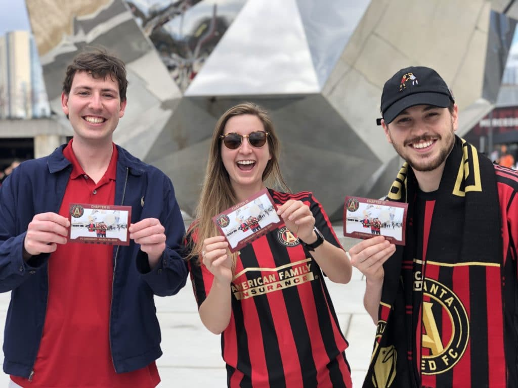 Three fans holding Mag-nificent photos outside of a soccer game.