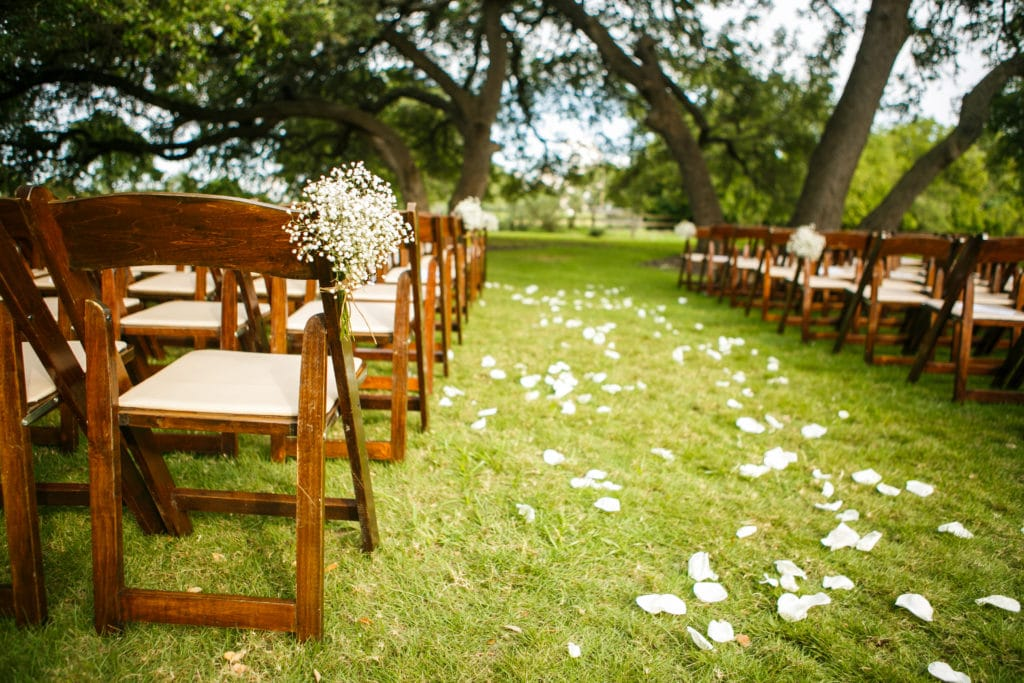 Outdoor wedding setup with flower petals going down the aisle.