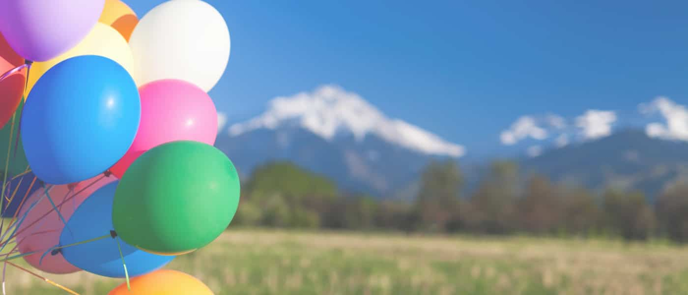 Birthday balloons floating in front of a mountain backdrop outside of Denver.